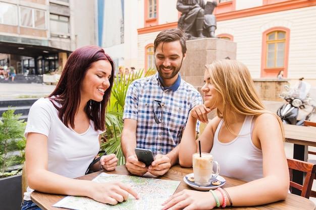 Grupo de amigos sentados no restaurante à procura de direção no smartphone Foto gratuita
