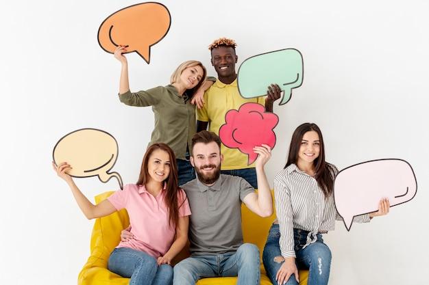 Grupo de amigos sorridente segurando bolhas do bate-papo Foto gratuita
