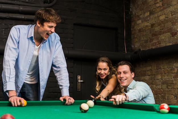 Grupo de amigos sorridentes jogando sinuca desfrutando no clube Foto gratuita