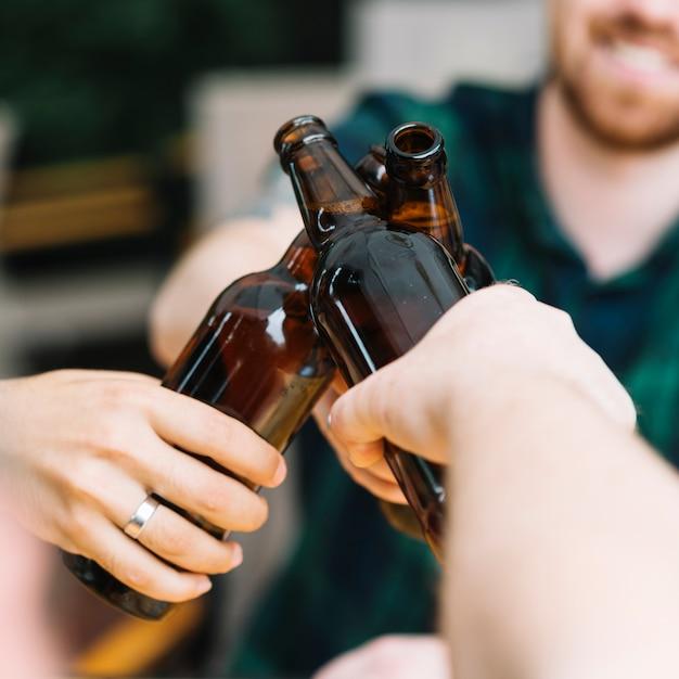 Grupo de amigos tilintando as garrafas de cerveja marrom Foto gratuita