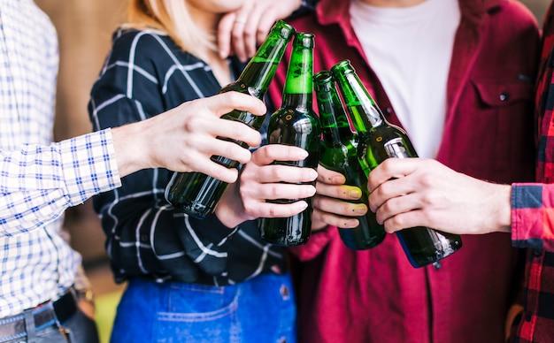 Grupo de amigos tilintando garrafas de cerveja Foto gratuita