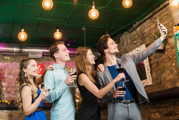 Grupo de amigos tomando selfie no celular em festa Foto gratuita
