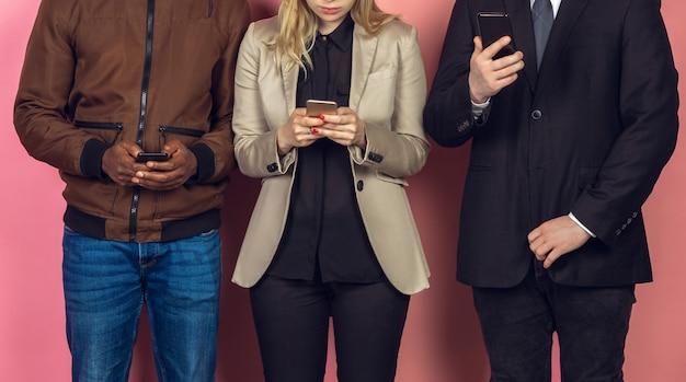 Grupo de amigos usando smartphones móveis. vício dos adolescentes nas novas tendências tecnológicas. fechar-se. Foto gratuita