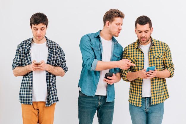 Grupo de amigos usando telefone celular contra o pano de fundo branco Foto gratuita
