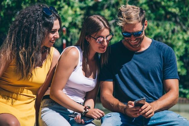 Grupo de amigos usando telefone móvel esperto - conceito de dependência. Foto Premium