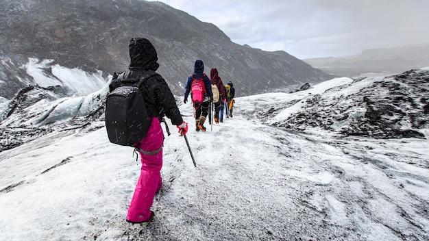 Grupo de andar de pedestrianismo na geleira durante a neve em solheimajokull Foto Premium