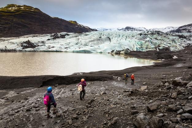 Grupo de caminhantes caminhando para geleira com guia Foto Premium