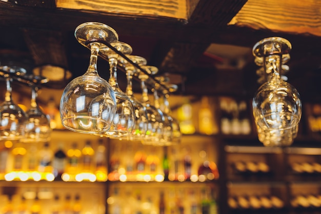 Grupo de copos de vinho vazios pendurados em vigas de metal em um bar. Foto Premium