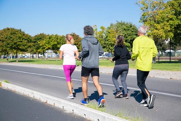 Grupo de corredores maduros com roupas esportivas, correndo lá fora, treinando para a maratona, aproveitando o treino matinal. tiro de corpo inteiro. aposentados e conceito de estilo de vida ativo Foto gratuita