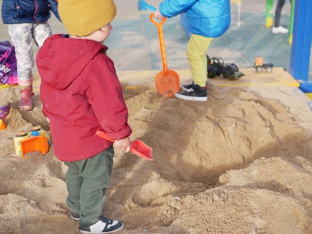 Grupo de crianças brincam na caixa de areia Foto Premium