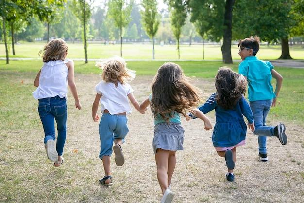 Grupo de crianças correndo na grama juntos, tendo uma corrida no parque. vista traseira, comprimento total. conceito de atividade infantil ao ar livre Foto gratuita
