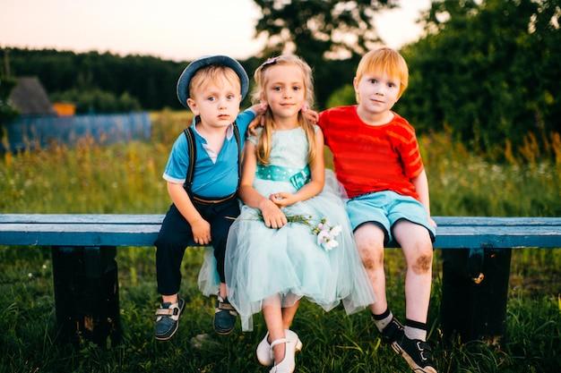 Grupo de crianças emocionais, sentado no banco ao ar livre na zona rural. garota de vestido entre dois rapazes. relações difíceis. ciúme da juventude. triângulo amoroso engraçado. alegria, tristeza, mágoa e ofensa Foto Premium