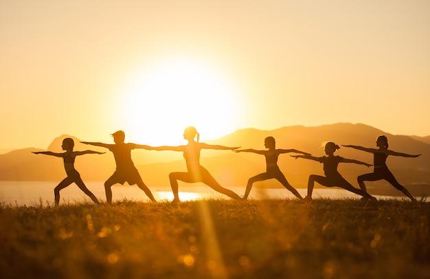 Grupo de crianças estão envolvidas em yoga com um treinador no oceano. Foto Premium