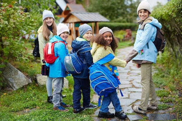 Grupo de crianças felizes, caminhando para a escola no outono Foto gratuita