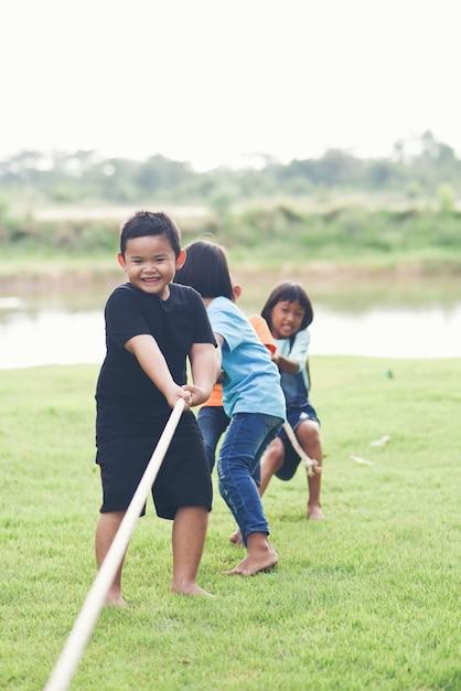 Grupo de crianças jogando cabo de guerra no parque Foto gratuita