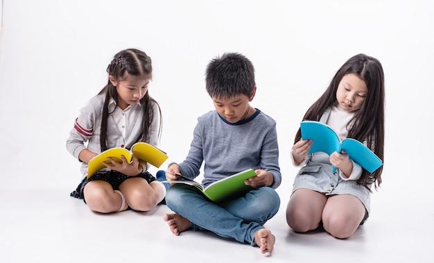 Grupo de crianças lendo livro juntos, com sentimento de interesse, fazendo atividade juntos Foto Premium