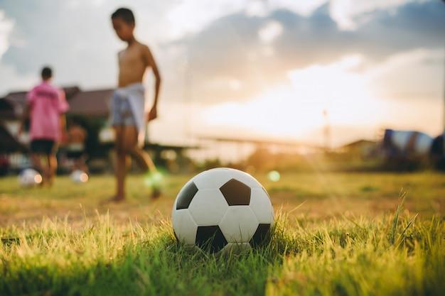 Grupo de crianças se divertindo jogando futebol de rua para exercício em área rural comunitária Foto Premium