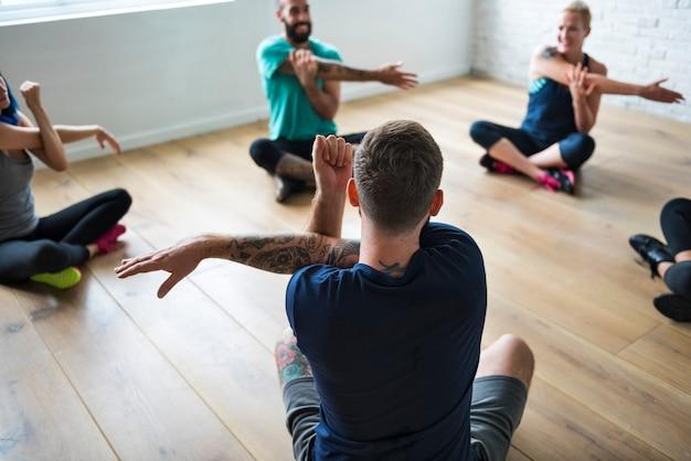 Grupo de diversas pessoas estão se juntando a uma aula de ioga Foto Premium