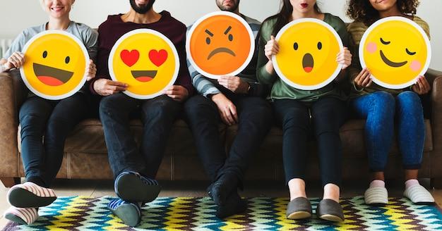 Grupo de diversas pessoas segurando ícones de emoticon Foto Premium