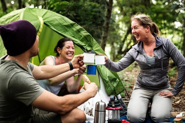 Grupo de diversos amigos, acampar na floresta Foto Premium