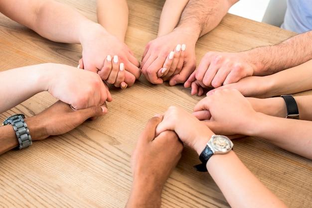 Grupo de diversos amigos, segurando suas mãos juntas sobre a mesa de madeira Foto gratuita