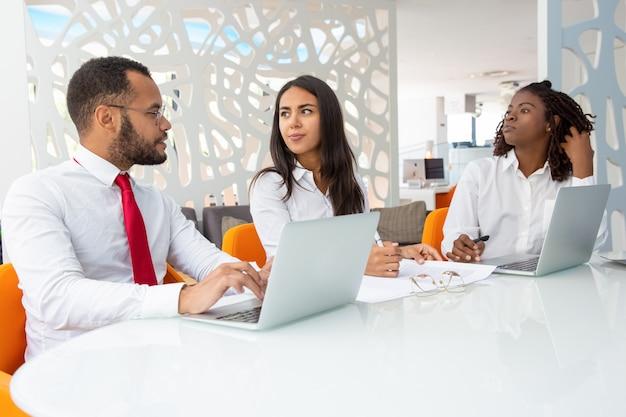 Grupo de empresários falando durante reunião Foto gratuita
