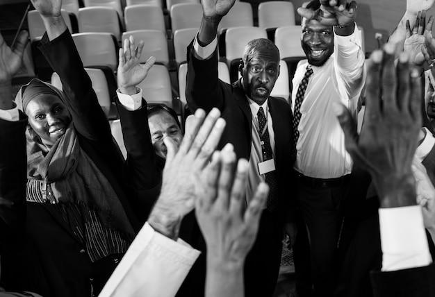 Grupo de empresários internacionais, levantando as mãos Foto gratuita