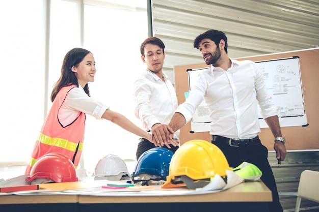 Grupo de engenheiros com juntar mão juntos no conceito de trabalho em equipe. Foto Premium