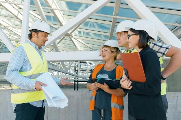 Grupo de engenheiros, construtores, arquitetos no canteiro de obras Foto Premium