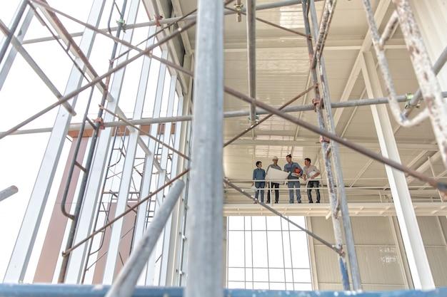 Grupo de engenheiros, homem e mulher, trabalhando juntos no canteiro de obras Foto Premium