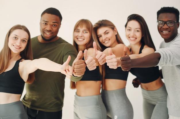Grupo de esportes em pé em uma parede branca Foto gratuita