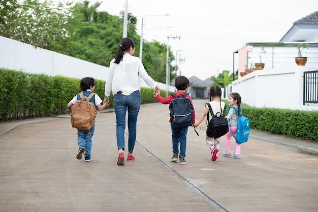 Grupo de estudante pré-escolar e professor de mãos dadas e caminhando para casa. Foto Premium