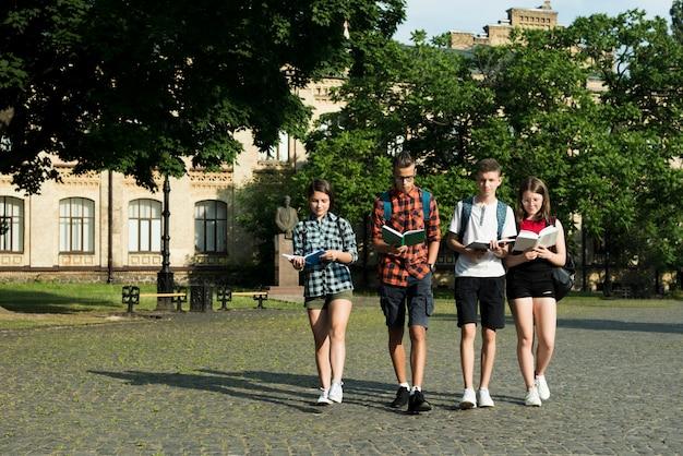 Grupo de estudantes do ensino médio lendo enquanto caminhava Foto gratuita