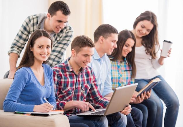 Grupo de estudantes estão sentados no sofá. Foto Premium
