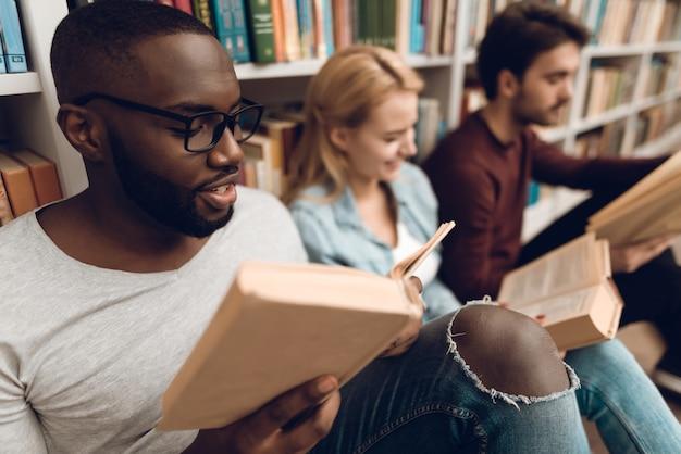 Grupo de estudantes multiculturais étnicos sentado na biblioteca. Foto Premium