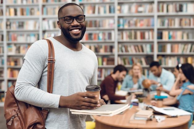 Grupo de estudantes na biblioteca e cara preta com café. Foto Premium