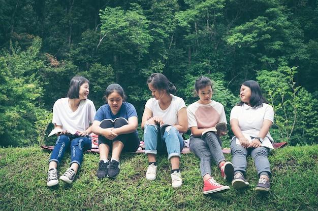 Grupo de estudantes sentados na grama Foto Premium
