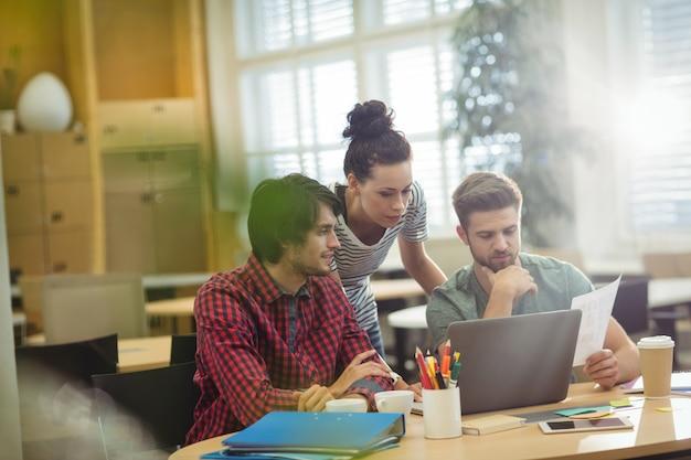 Grupo de executivos que discutem sobre laptop em sua des Foto gratuita