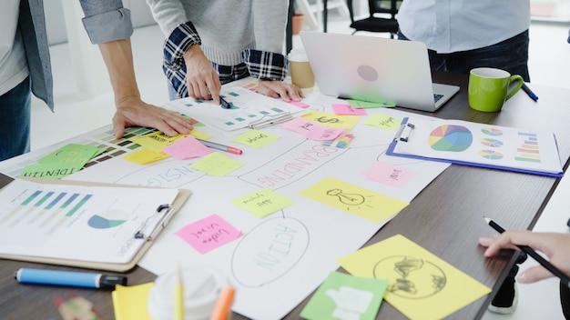 Grupo de executivos vestidos ocasionalmente que discutem ideias no escritório. Foto gratuita