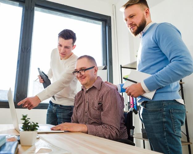 Grupo de homens adultos trabalhando juntos no escritório Foto gratuita