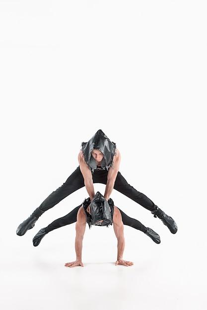 Grupo de homens caucasianos acrobáticos ginásticos na pose de equilíbrio Foto gratuita