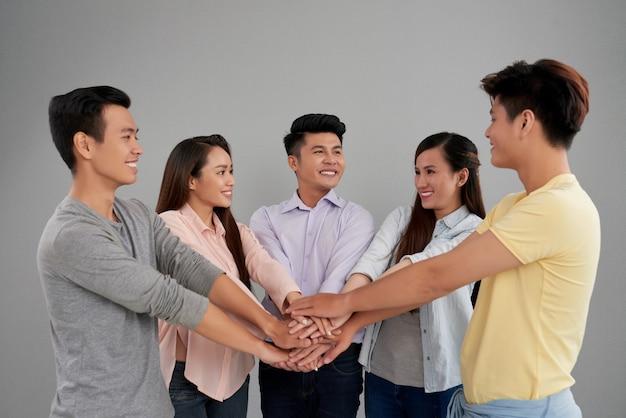 Grupo de homens e mulheres asiáticos posando e unir as mãos Foto gratuita