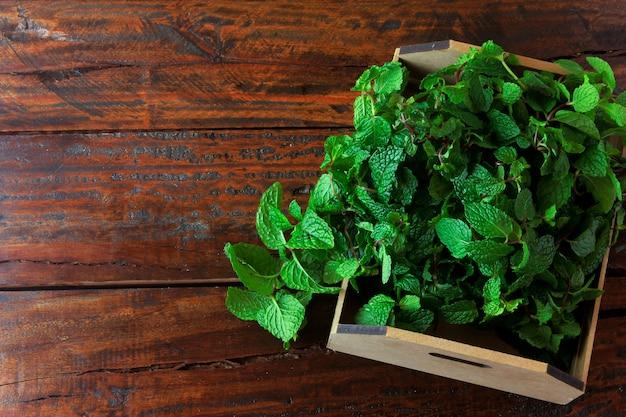 Grupo de hortelã fresca orgânica verde no cesto sobre a mesa de madeira rústica Foto Premium