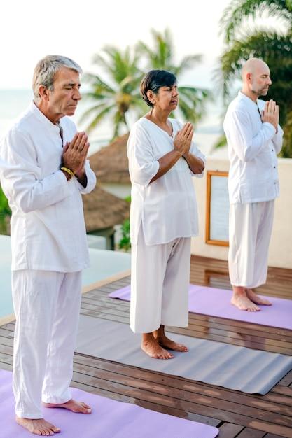 Grupo de idosos praticando ioga à beira da piscina Foto Premium