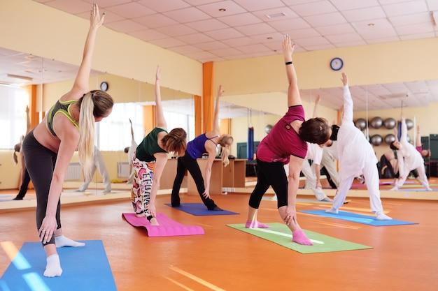 Grupo de ioga realiza asanas Foto Premium