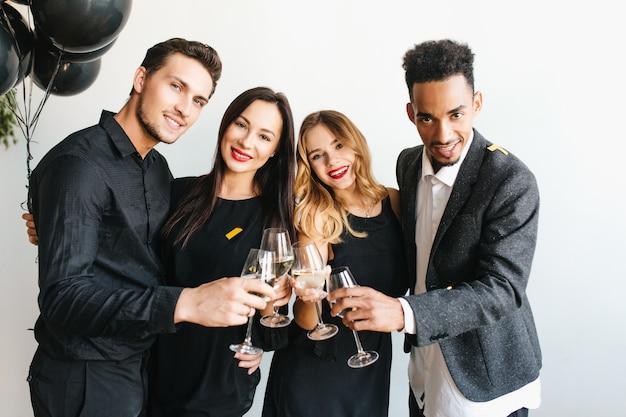 Grupo de jovens alegres em trajes da moda levantando taças com champanhe Foto gratuita