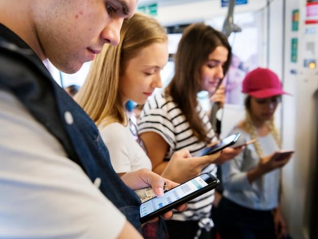 Grupo de jovens amigos adultos usando smartphones no metrô Foto Premium