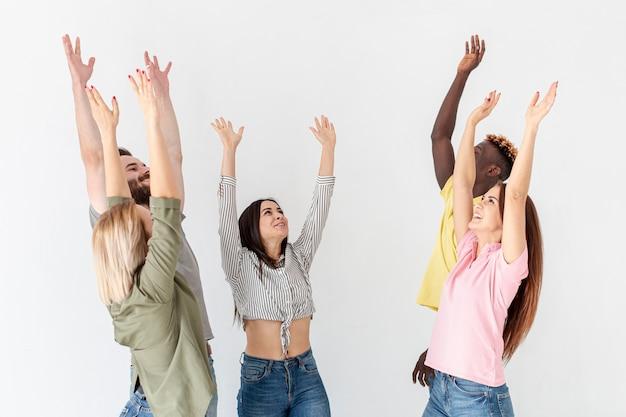 Grupo de jovens amigos com as mãos levantadas acima Foto gratuita