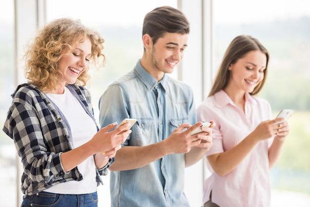 Grupo de jovens amigos positivos usando seus telefones. Foto Premium