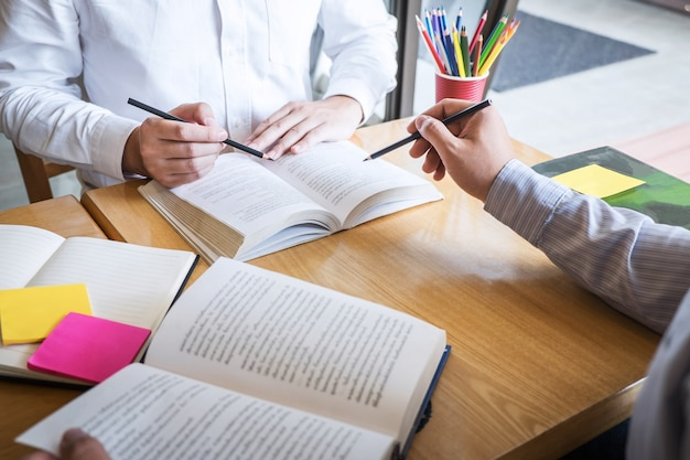 Grupo de jovens aprendendo a estudar nova lição para o conhecimento na biblioteca durante o ensino da educação de amigos na preparação para o exame Foto Premium
